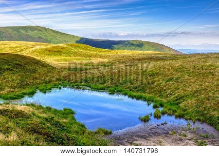 summer landscape in mountains with small swamp on hill side