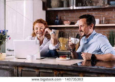 Look here. Relaxed woman and interested man looking at the laptop while sitting at the table in the kitchen