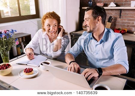Busy time. Delighted woman talking on the phone and taking notes while her husband working on laptop in the kitchen