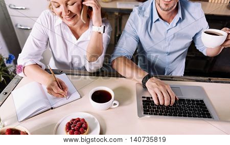Involved in work. Top view of a woman receiving a call and taking notes while a man drinking coffee and working on a laptop