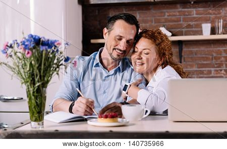 Great idea. Satisfied woman cuddling his delighted bearded man and looking at the notebook where he explaining his new idea while sitting in their kitchen