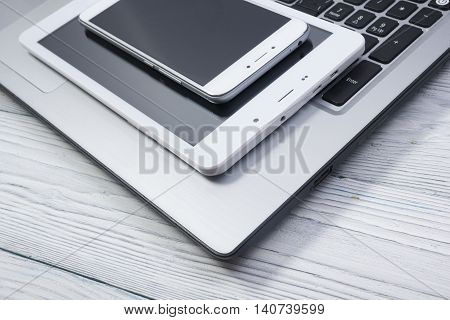 set of modern computer devices - laptop, tablet and phone close up.