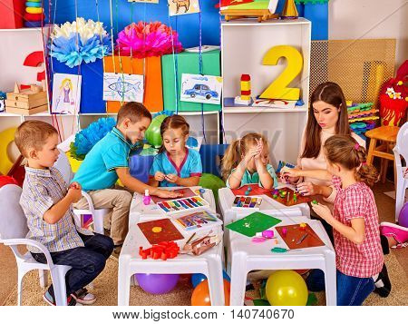 Group clever children with young beautiful teacher mold from plasticine in primary school. Children school education.