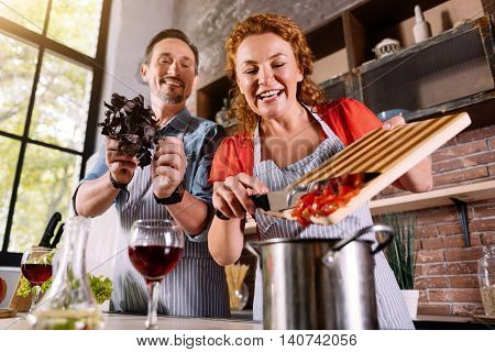 Lets add a favor. Smiling woman adding a cut vegetable to a pot while his husband advising to add basilica