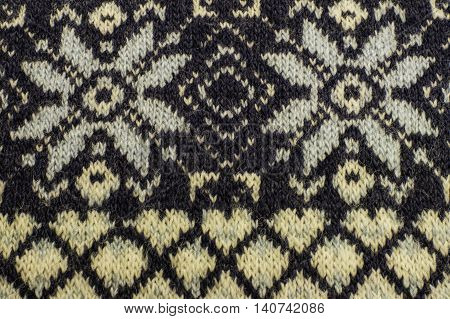 Real knitted fabric textured background. Knitted pattern with snowflakes.