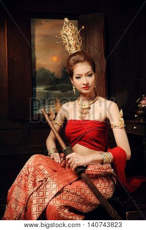 Thai woman dressing traditional costume sit next to window hold sword in thai old house style.