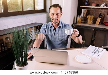 Lets look here. Pleasant amiable mature man using the laptop while sitting at the in the kitchen
