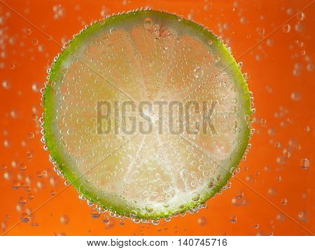 lime in soda water on orange background