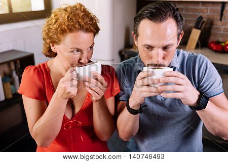 Funny morning. Cute middle aged couple drinking coffee and holding cups near mouth