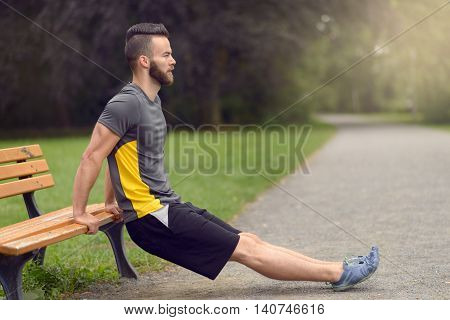 Young Man Exercising Using A Wooden Park Bench