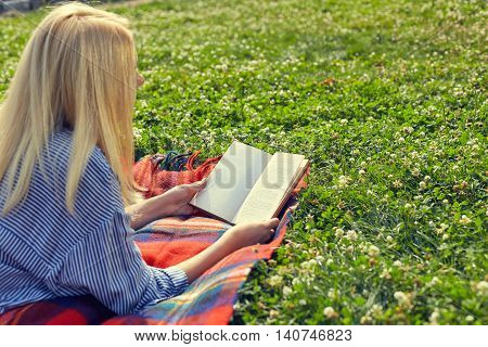 View from the back of a girl reading a book on green grass in park. Young woman with book lying and relaxing in the sunny blooming grass. A woman thinking about book and enjoy.