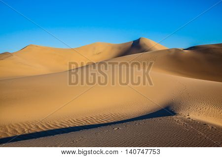Bizarre twists of orange sand dunes. Mesquite Flat Sand Dunes. Sunny morning in a picturesque part of Death Valley, USA