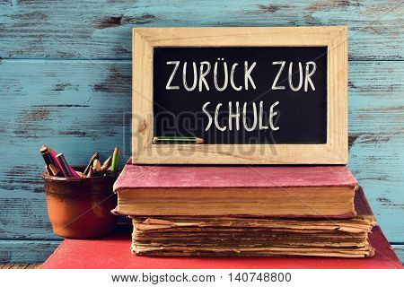 closeup a chalkboard with the text zuruck zur schule, back to school written in German, on a pile of old books and a pot with some pencils, against a rustic blue wooden background