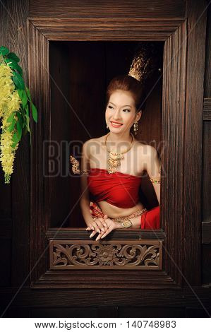 Thai Woman Dressing Traditional Costume Stand Next To Window In Thai Old House.