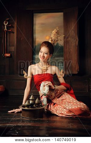 Thai Woman Dressing Traditional Costume Sit Next To Window Hold Flower Floral In Thai Old House Styl