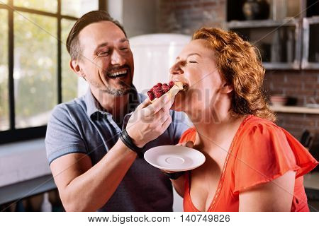 This cake is from paradise. Close up of a laughing man giving to taste a cake to his pretty woman