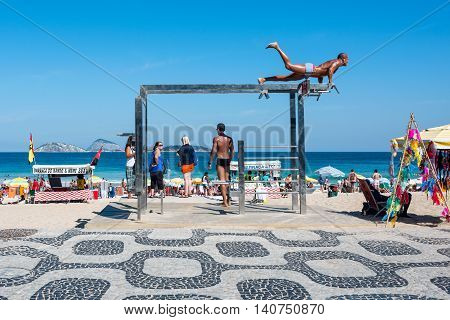 Rio de Janeiro Brazil - July 24 2016: Young man at one of the many outdoor fitness stations on Ipanema Beach