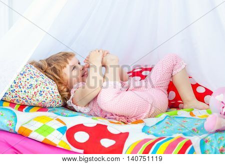 Little cute curly girl in pink pajamas lying in a baby bed with a canopy and trying to get the leg up to the nose.