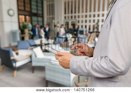 Businessman Use Wireless Tablet Device In Party At Restaurant With Bokeh