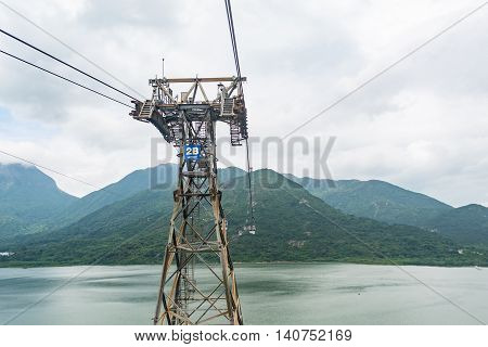 HONG KONG - MAY 26: A metallic tower of the Ngong Ping 360 cable car stands in Tung Chung bay in the cloudy day on May 26 2016 in Hong Kong.