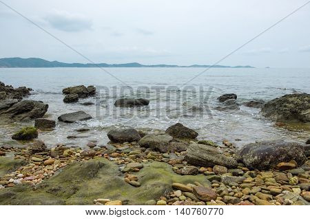 View of a sea coastline with stones and rocks at Khao Laem Ya Mu Ko Samet National Park in Thailand.