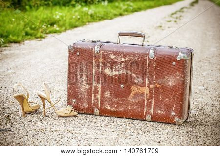 Old suitcase and high heel sandals on the rural road