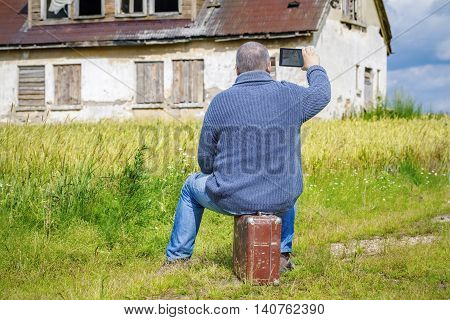 Man sitting on suitcase and take pictures of old house