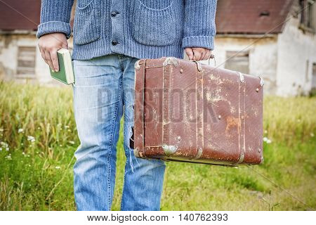 Man with suitcase and book in summer day