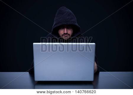 Hacker is working in front of his computer monitor