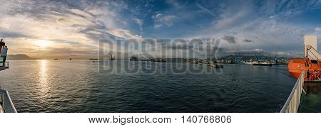 A panorama of the port of Algeciras on the right side and Gibraltar and an awesome sunset on the left side. The weather is aweosme with blue sky and some clouds and some containerships on the water.