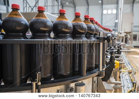 Close up of plastic beer bottle industry on a conveyor belt