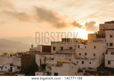 Close up of some old houses in the city of Tetouan in Morocco at sunset. The sky is golden and there are few clouds in the sky.