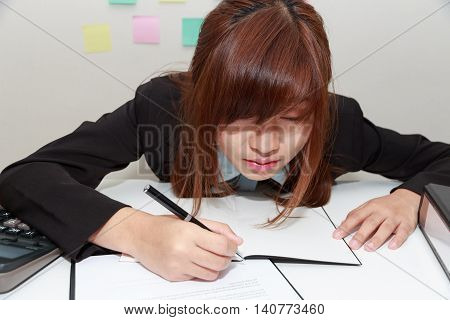 Sleepy and tired business woman at desk holding a pen for writing and close her eyes - business concept