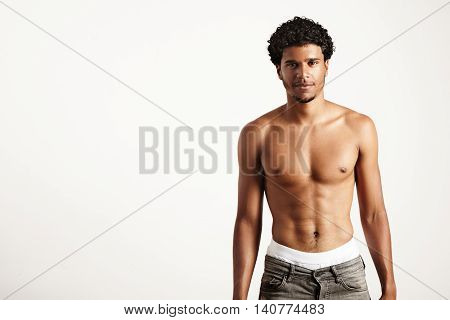 young smiling man wears jeans topless on a white background
