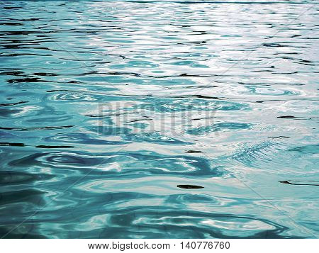 reflection of light on the waves , blue water and light from the sun in pool , water level ,blue abstract background