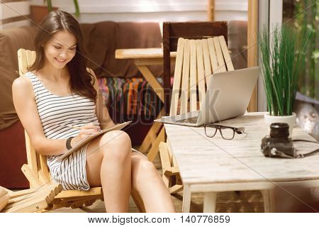 Put it down. Cheerful beautiful young woman making notes and sitting in the chair while working at home