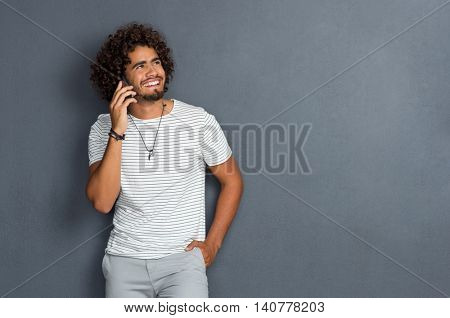 Cool man with beard talking on phone and looking up. Casual young man talking on the smartphone and smiling on grey background with copy space. Portrait of a young african man talking over phone.