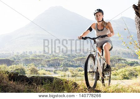 Portrait of senior woman riding mountain bike in countryside. Active mature woman riding cycle in nature while listening to music with mp3 player. Healthy sporty woman riding her bicycle at park.