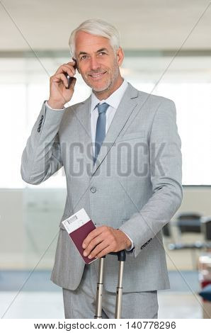 Portrait of a senior business man talking on mobile phone at airport lounge. Portrait of a senior businessman travelling with passport and  luggage, talking at cellphone.