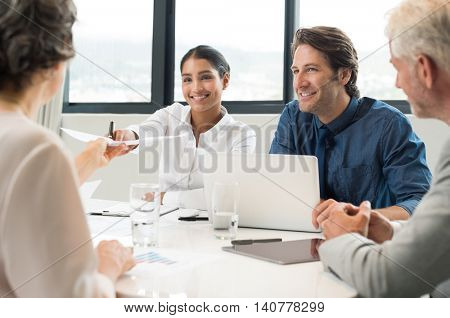 Cheerful businesswoman giving report to senior manager. Happy businessmen and businesswomen in a meeting. Young marketing manager handing over report of month sales to executive.