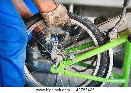 replacement bicycle wheels. replacing tires on a bicycle in a repair service. Worker repairing children's  bike. closeup. side view