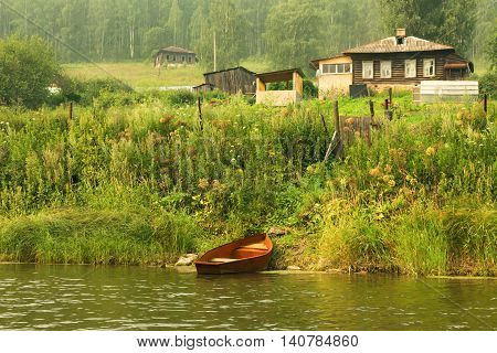 Steel Fishing Rowboat In Red Next To A Wooden House