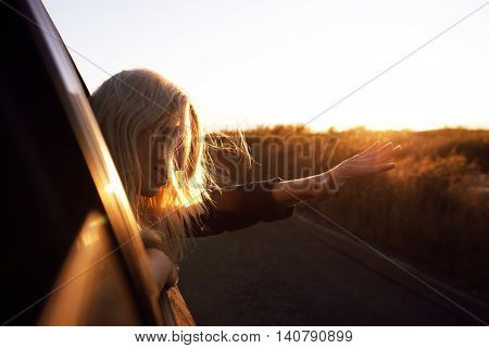 young woman waving out of car window in sunset