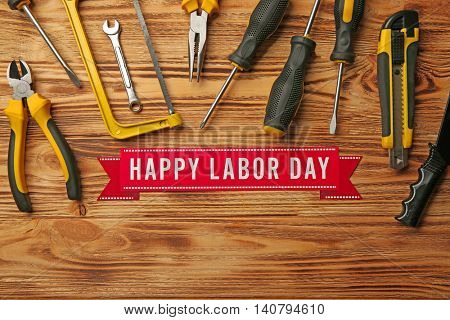Happy Labor Day holiday and tools set on wooden background
