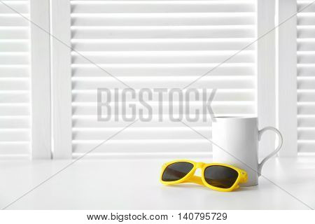 Cup and sunglasses on white folding screen background