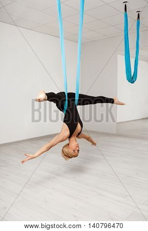 Young beautiful blonde girl practicing aerial yoga in gym.