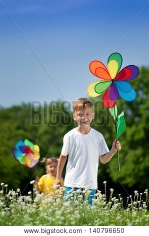Happy children - boy and girl with colorful weathercock walking on a meadow in sunny day