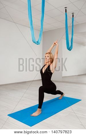 Young beautiful sportive blonde girl practicing yoga in gym.