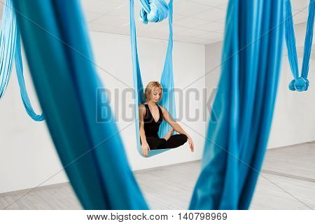 Young beautiful blonde girl smiling, practicing aerial yoga in gym.