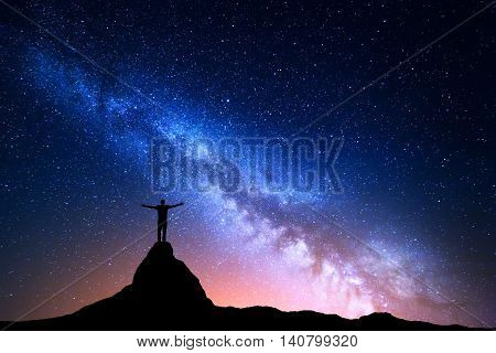 Night landscape with Milky Way. Silhouette of a standing man with raised up arms on the top of mountain. High rocks mountain peak. Beautiful Galaxy. Universe. Blue night starry sky and city lights